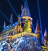 Hogwarts castle lit up with nighttime projections during the holidays at Universal Orlando